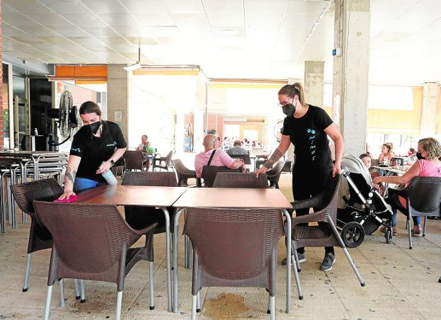 Waitresses clean a table in a cafeteria in the San José neighborhood, yesterday.