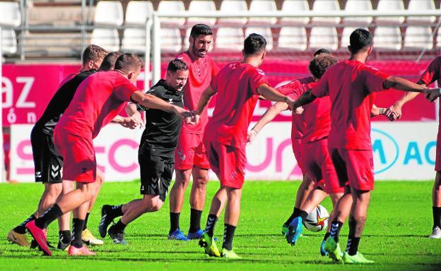 Mario Simón, en el centro, junto a algunos futbolistas de su plantilla en un entrenamiento en el Enrique Roca.