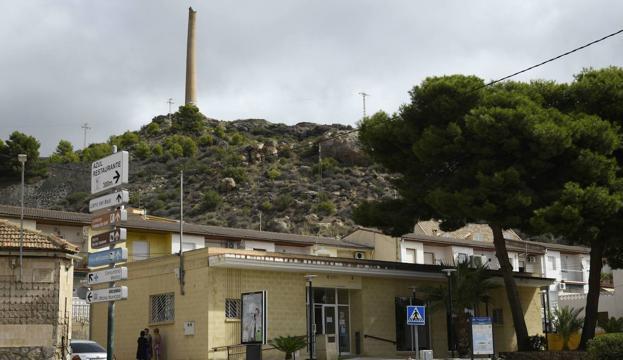 Vista del centro de salud de Portmán (La Unión), situado cerca de una antigua fundición de plomo, de la que se conserva la chimenea. / ANTONIO GIL / AGM