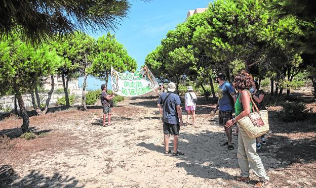 Recorrido de varios de los ciudadanos concentrados con una pancarta, ayer, por el terreno en el que está previsto el edificio. / J. M. RODRÍGUEZ / AGM